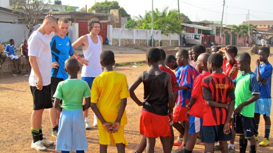 Volunteer coaches take their students through new football strategies in Ghana.